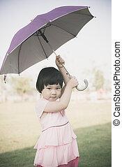 Happy Asian girl holding umbrella outdoor.