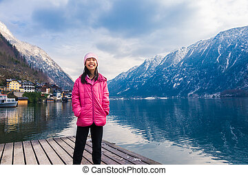 Happy asian girl in pink winter cloth staning by a lake with blurred town and mountain range across the water in background