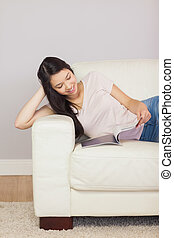 Happy asian girl lying on the sofa reading a magazine