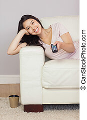Happy asian girl lying on the sofa watching tv