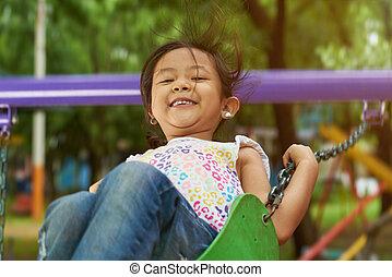 Happy asian girl on swings