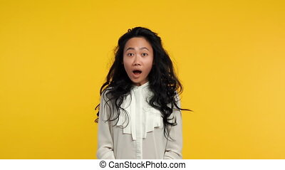 Happy asian girl showing thumbs up on yellow background....