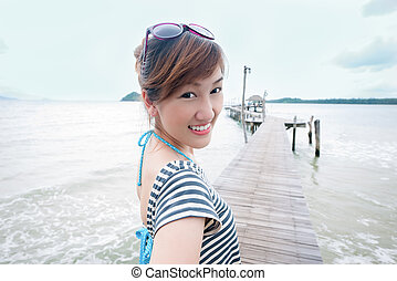 Happy asian girl to the sea