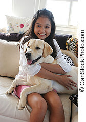 Happy Asian girl on animal print sofa with her pet dog