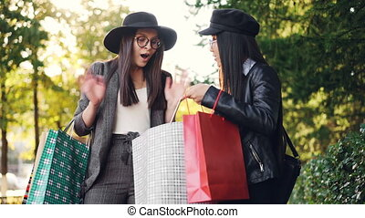 Happy Asian girl with shopping bags is talking to her friend standing in the street then showing her purchases while Caucasian young woman is expressing positive emotons.