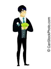 Happy asian groom holding money.