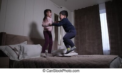 Happy asian kids having fun jumping on bed at home