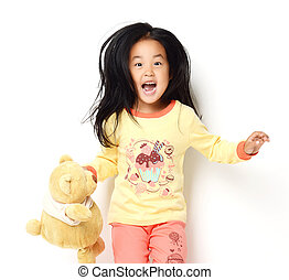 Happy asian korean girl with teddy bear standing yelling and looking