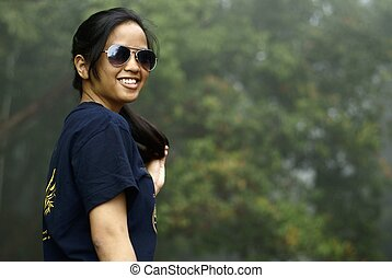 Happy asian malay teen lady with sunglasses outdoors