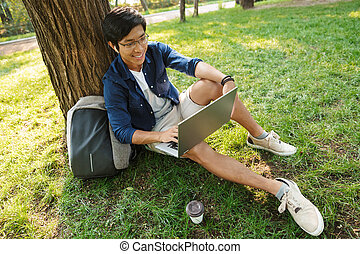 Happy asian male student in eyeglasses using laptop computer