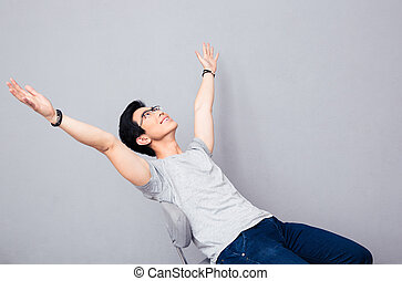 Happy asian man dreaming over gray background