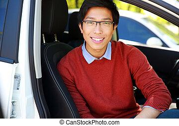 Happy asian man in glasses sitting in car