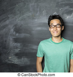 Happy Asian man looking to left next to a blackboard. -...