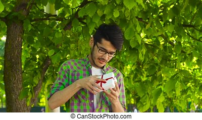 Happy asian man opening gift in park - Asian guy smiling and...