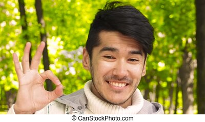 Happy asian man show OK sign to camera and smiling in front...