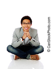 Happy asian man sitting on the floor over white background