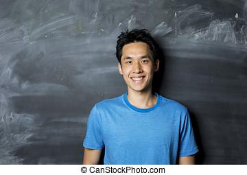 Happy Asian man standing next to a blackboard.