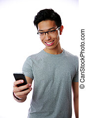 Happy asian man using smartphone on gray background