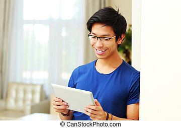 Happy asian man using tablet computer at home