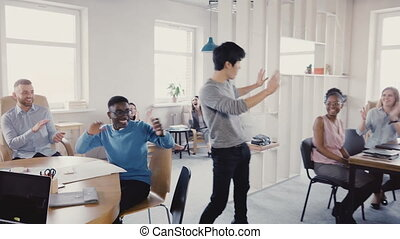 Happy Asian manager doing very funny celebration dance walk in modern office, multi-ethnic colleagues clap and laugh 4K.