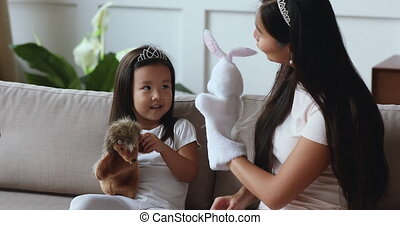 Happy asian mom and child daughter playing puppet toys