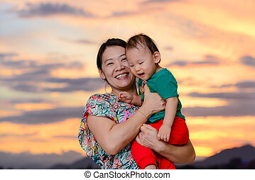 Happy Asian mother and baby with sun set background.