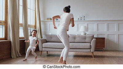 Happy asian mother and daughter having fun in living room