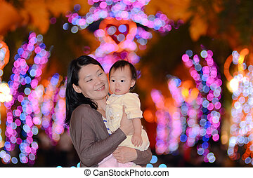 Happy Asian mother and her baby with christmas light background.