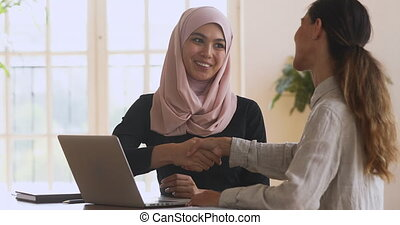 Happy asian muslim manager handshaking caucasian female client at meeting