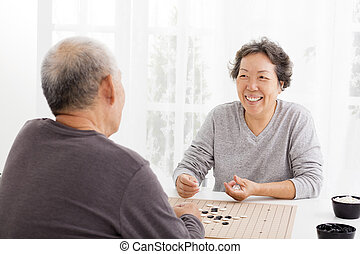 happy asian senior couple playing chess in living room
