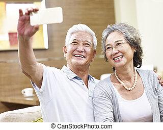 happy asian senior couple taking a selfie