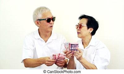 happy Asian senior couple with cash
