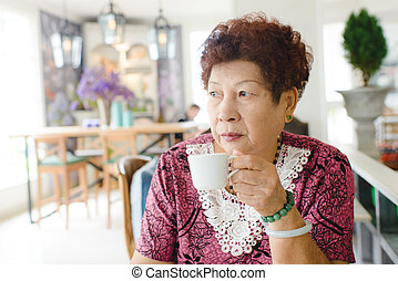 Happy Asian senior woman drinking tea at cafe.