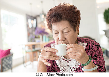 Happy Asian senior woman drinking tea at home.