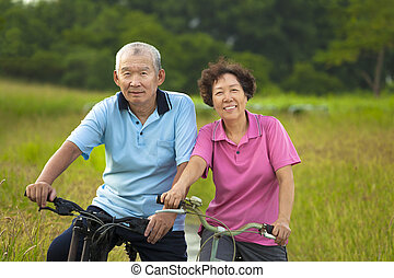 Happy Asian seniors couple biking in Park.