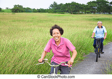 Happy asian seniors couple biking in the park.
