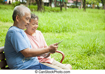 happy asian seniors couple with tablet pc
