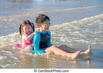 Happy asian siblings playing on the beach