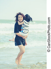 Happy Asian sister and child on the beach.