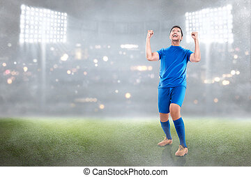 Happy asian soccer player man celebrate the victory