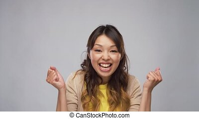 happy asian woman celebrating success