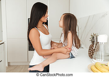 Happy asian woman cooking with her little daughter together