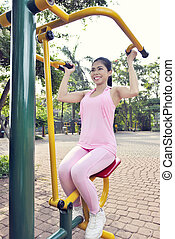 Happy asian woman doing fitness workout with weights machine