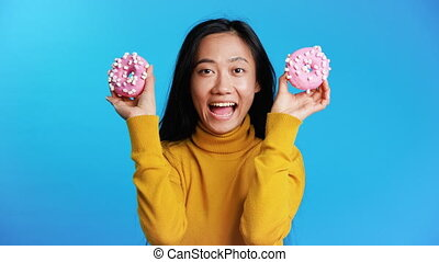 Happy asian woman having fun with donuts. Girl showing ...