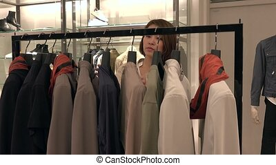Happy Asian Woman Looking At Clothes Rack In Fashion Shop -...