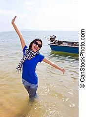 Happy Asian woman on the beach