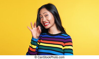 Happy asian woman showing ok sign on yellow background. Good idea concept