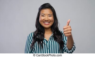 happy asian woman showing thumbs up over grey - people, ...