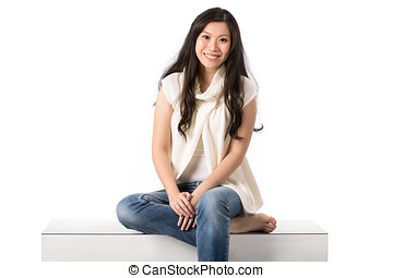 Happy Asian woman sitting on a bench. - Happy Asian woman in...