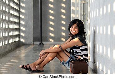 Happy asian woman sitting on corridor floor